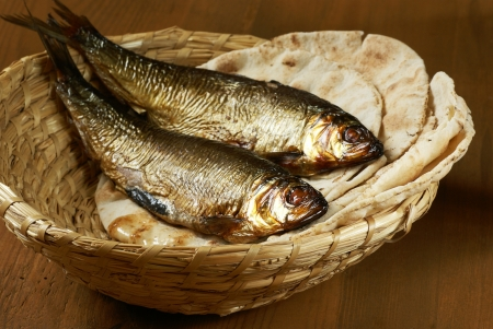 Loaves of bread and two fishes in a basket. photo