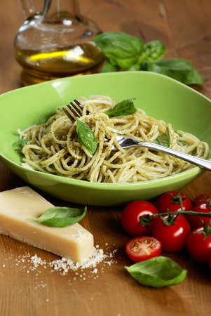 Plate with cooked spaghetti with basil pesto and cooking ingredients. photo