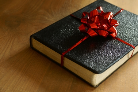 bible christmas: Bible with ribbon as a gift on wooden background.