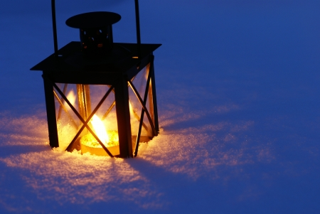 lantern: Lantern with burning candle on snow in the evening.