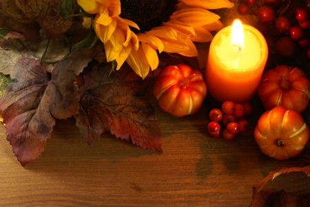 Arrangement of sunflower, candle and autumn decorations on wooden background with copy space. Stock Photo