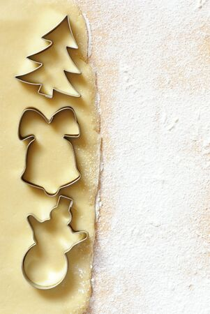 Dough for Christmas cookies and cookie cutters. Background with copy space photo