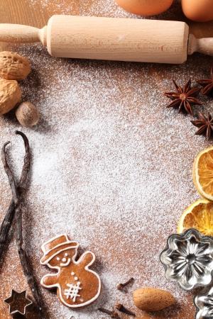 biscotti di natale: Utensili di cottura, spezie e ingredienti alimentari su sfondo di legno con copia spazio.