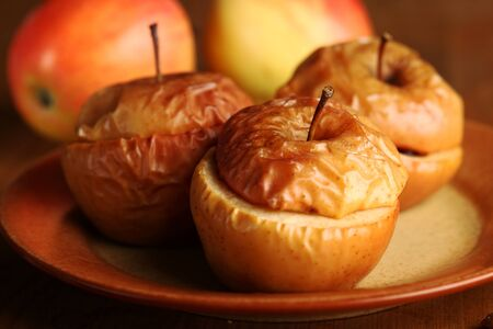 Close-up of baked apples with fresh apples in the background. Selective focus, shallow DOF.