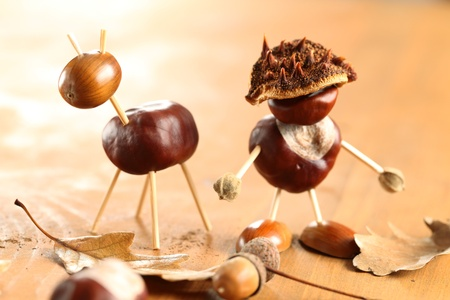 Chestnut and acorn figurines on wooden table. Selective focus, shallow DOF.