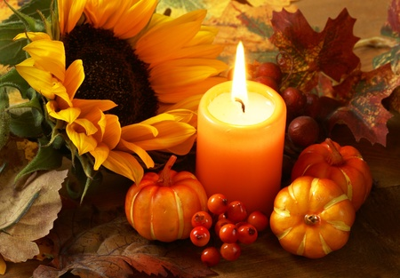 Arrangement of sunflower, candle and autumn decorations photo