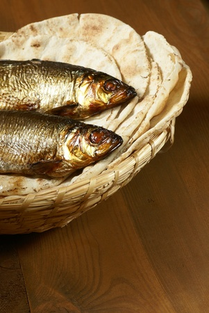 Loaves of bread and two fishes in a basket photo