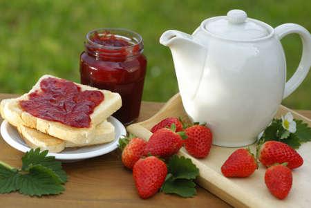light breakfast: Mug, toast, glass with strawberry jam and strawberries Stock Photo