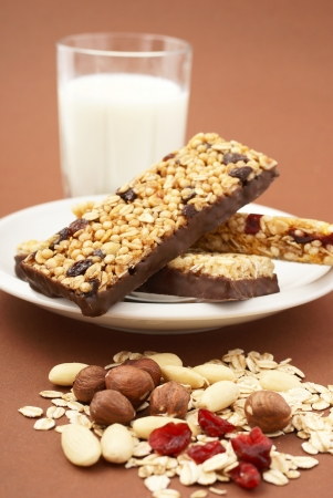 cereal bar: Granola bar, almonds, nuts, dry cranberries, oat flakes and glass of milk
