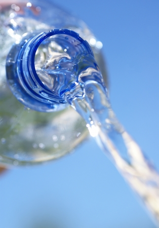 pour water: Close-up of bottle with pouring water. Selective focus, shallow DOF,copy space.