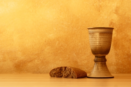 Chalice with wine and bread. Background with copy space. photo