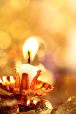 gold en: Candle and defocused abstract background