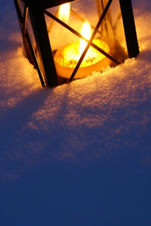 Lantern with burning candle on snow