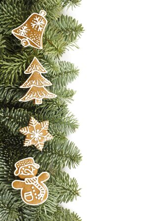 Holiday frame with branches and gingerbread cookies on white background photo