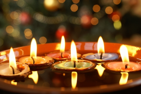 nutshells: Candles in nutshells floating on water with Christmas background. Stock Photo