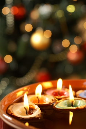 lights: Candles in nutshells floating on water with Christmas background. Stock Photo