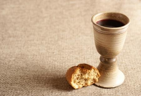 COMUNION: Cáliz con el vino y el pan. Fondo con el espacio de la copia Foto de archivo
