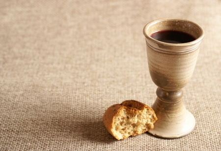Chalice with wine and bread. Background with copy space