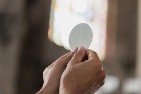 comunion: Detalle de las manos con el pan de la comunión. Foto de archivo