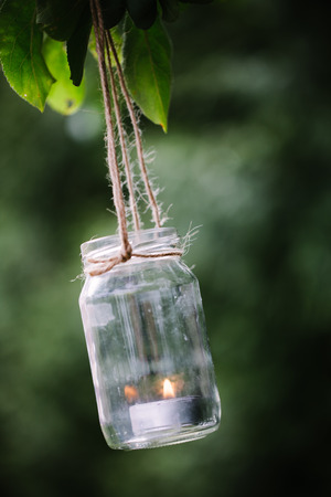 Jar with burning candle hanging on a tree. Stock Photo