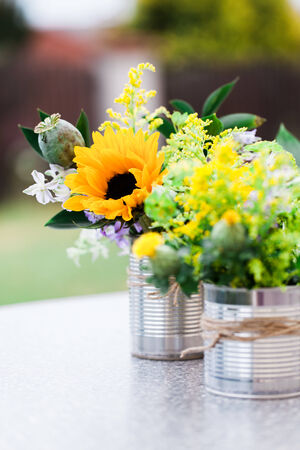 arranging: Wild flowers in cane vase on a garden table