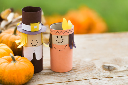 indian thanksgiving: Pilgrim and Indian decorations on a wooden table. Stock Photo