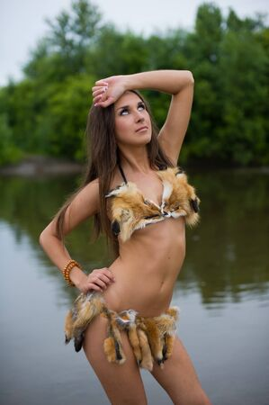 Savage poses in swimsuit near river photo