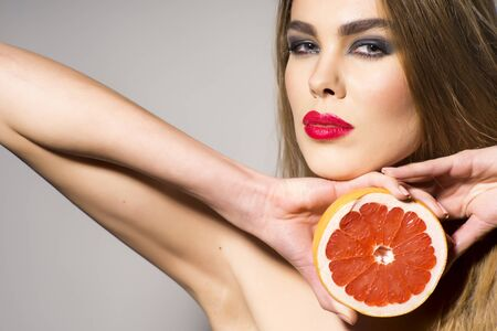 the next life: Young woman holding grapefruit cut in half next to the head , healthy life concept photoset of attractive girl holding a cut piece of pomelo in her hands Stock Photo