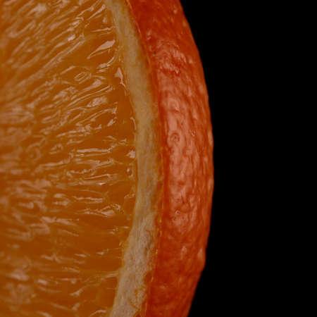 gustatory: Juicy orange slice on black background close-up Stock Photo