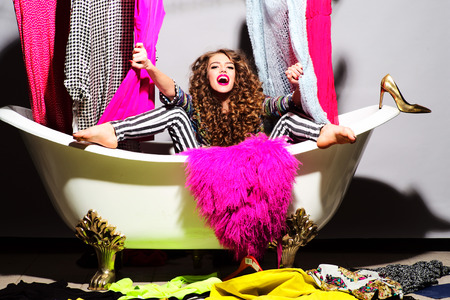 Young beautiful fashionable woman with curly hair in bathtub with colorful clothing Imagens