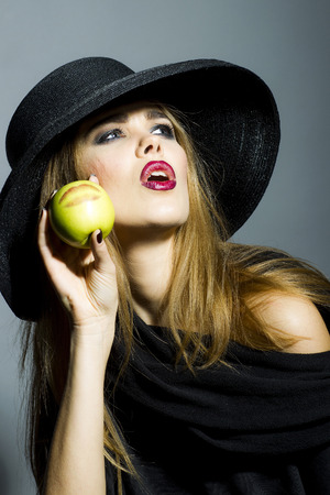 Elegant fashionable woman in black hat holding green apple with kiss photo