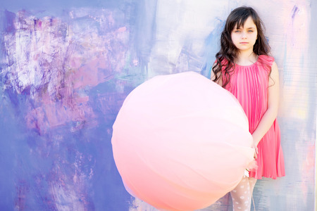 beautiful preteen girl: Nice little girl holding light-orange balloon looking forward on bright background, copyspace horizontal photo