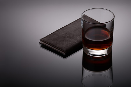Glass of whiskey and a business card holder on reflective dark background photo