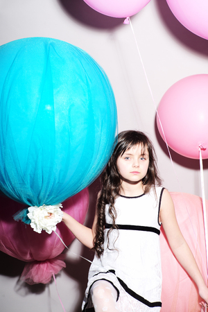 Little cutie sitting with balloons looking forward, vertical picture 免版税图像