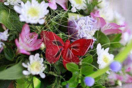 flowers horizontal: Red butterfly in bright bouquet of colorful flowers, horizontal picture