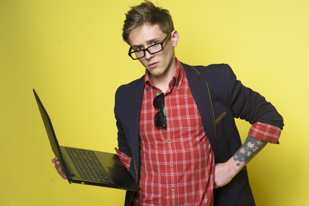 studing: Smart guy in glasses holding computer standing and looking forward on yellow background, horizontal picture