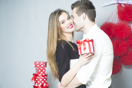 heart gift box: Romantic couple of young people embraces and standing close to each other holding gift, horizontal photo