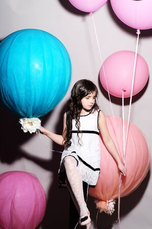 cutie: Small cutie sitting looking away and holding balloons, vertical picture