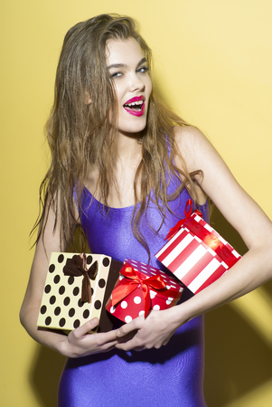 Playful smiling girl in violet jumpsuit holding colorful boxes of presents standing on yellow background, vertical photo photo