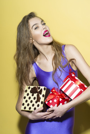 exalted: Exalted smiling girl in violet jumpsuit holding colorful boxes of presents standing on yellow background, vertical photo Stock Photo