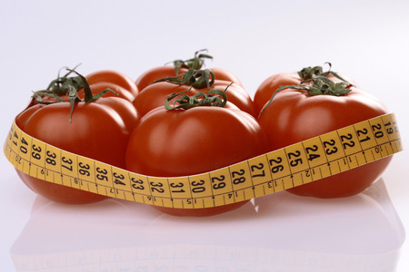 reflective: Ripe tomatoes and measuring tape on light reflective background Stock Photo