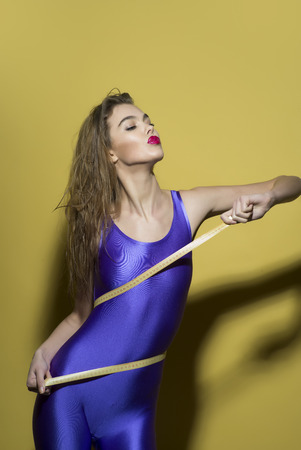 lycra: Young girl in violet second skin jumpsuit standing with tape-line around torso on yellow background looking away, vertical picture Stock Photo