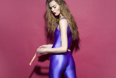 jumpsuit: Stylish slim girl in violet second skin jumpsuit standing on her back with tape-line around torso on purple background copyspace, horizontal picture