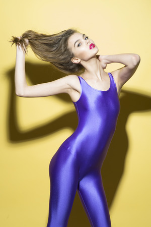 jumpsuit: Slim young girl; in violet jumpsuit holding her hair up standing on yellow background looking forward, vertical picture Stock Photo