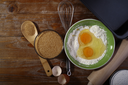 Ingredients and appliances for cooking on wooden table top with yolk in flour copyspace, horizontal picture photo