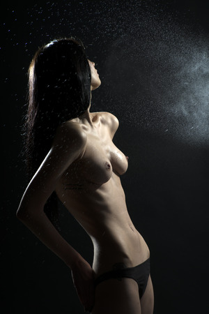 aqua naked: Undressed girl in spray looking away on black background, vertical picture