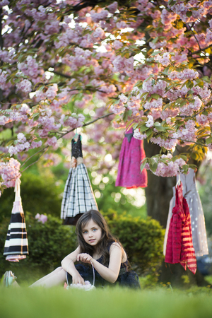 tree vertical: Little brunette girl with basket looking forward sitting in the garden among colorful baby dresses hanging in the japanese cherry blossom tree, vertical picture