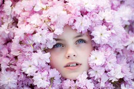 copyspase: Face of little girl with opened blue eyes among pink flowers of japanese cherry bloom copyspase, horizontal picture
