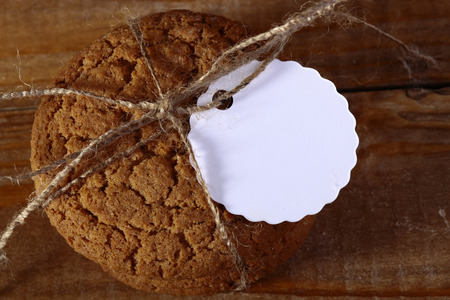 roped: Roped oatcake with tag laying on wood table top, horizontal picture