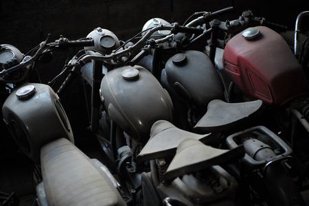 in row: Viejo negro y rojo de la motocicleta de pie en una fila en el garaje, cuadro horizontal Foto de archivo